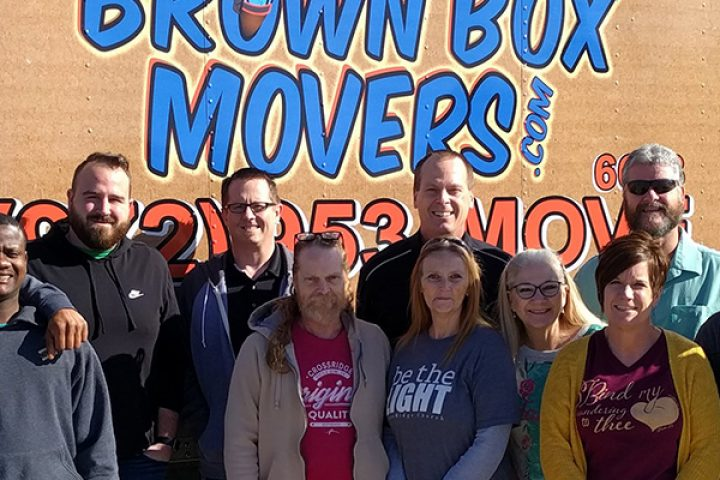 Staff of CrossRidge, Lovepacs, and Brown Box Movers standing front of Lovepacs delivery truck